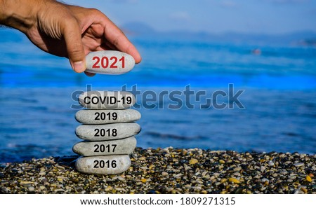 New Year 2021 is coming concept. Covid year change to 2021 background. Turn of old year concept. Happy new year 2021 replace Corona. New hopes, excitement with 2021. Man adding stone to pebble tower.