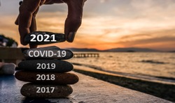 New Year 2021 is coming concept. Covid year 2020 to 2021 background. Positive turn of old year. Happy new year 2021 replace corona. New hopes, excitement with 2021. Man adding stone to pebble tower
