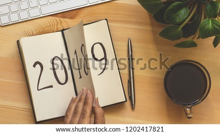 New Year 2019 is coming concept. Female hand flips notepad sheet on wooden table. 2018 is turning, 2019 is opening, top view, retro toned #1202417821