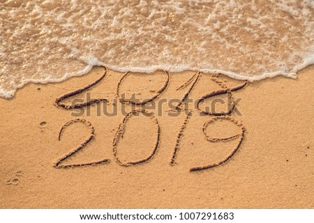 New Year 2019 is coming concept - inscription 2018 and 2019 on a beach sand, the wave is almost covering the digits 2018. #1007291683