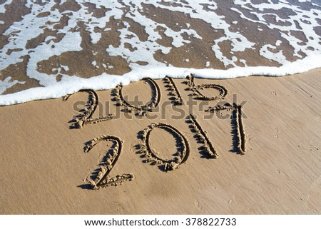 New Year 2017 is coming concept - inscription 2016 and 2017 on a beach sand, the wave is almost covering the digits 2016 #378822733