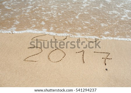 New Year 2017 is coming concept - inscription 2016 and 2017 on a beach sand, the wave is almost covering the digits 2016. #541294237