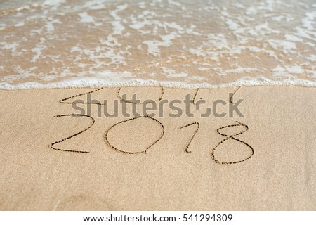 New Year 2018 is coming concept - inscription 2017 and 2018 on a beach sand, the wave is almost covering the digits 2017. #541294309