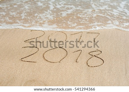 New Year 2018 is coming concept - inscription 2017 and 2018 on a beach sand, the wave is almost covering the digits 2017. #541294366