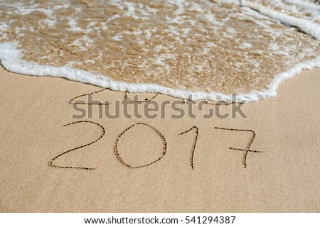 New Year 2017 is coming concept - inscription 2016 and 2017 on a beach sand, the wave is almost covering the digits 2016. #541294387