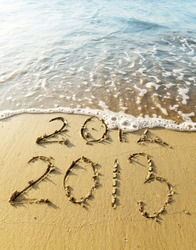 New Year 2013 is coming concept - inscription 2012 and 2013 on a beach sand, the wave is covering digits 2012.