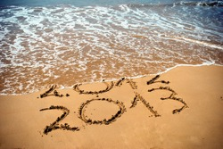 New Year 2013 is coming concept - inscription 2012 and 2013 on a beach sand, the wave is covering digits 2012