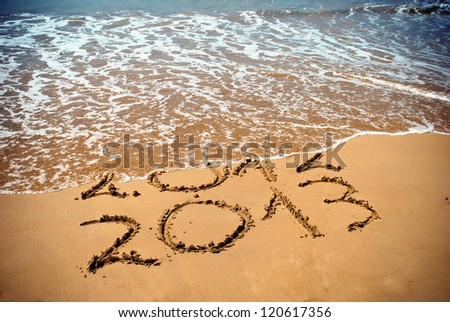 New Year 2013 is coming concept inscription 2012 and 2013 on a beach sand the wave is covering digits 2012
