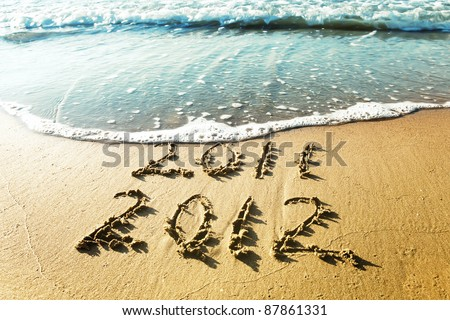 New Year 2012 is coming concept - inscription 2011 and 2012 on a beach sand, the wave is covering digits 2011. - stock photo