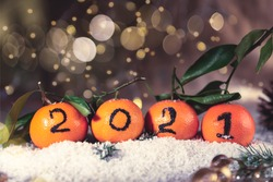 New Year 2021 is Coming Concept. Numbers written in Black Ink on the Oranges that are laying in the Basket with Pine Sticks and Xmas Lights on the Background