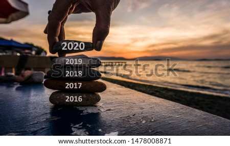 New Year 2020 is coming concept. Old year 2019 change to 2020 background. Turn of old year concept. Happy new year 2020 replace 2019. New hopes, excitement with 2020. Man adding stone to pebble tower.