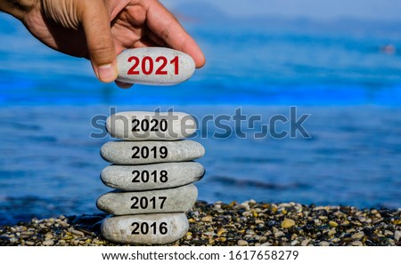 New Year 2021 is coming concept. Old year 2020 change to 2021 background. Turn of old year concept. Happy new year 2021 replace 2020. New hopes, excitement with 2021. Man adding stone to pebble tower.