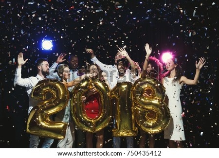 New 2018 year is coming! Group of cheerful young people in holding gold colored number balloons, showered with confetti. Christmas greeting card mokup, celebration concept
