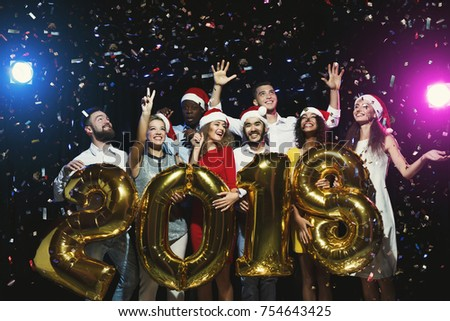 New 2018 year is coming! Group of cheerful young people in Santa hats holding gold colored number balloons, showered with confetti. Christmas greeting card mokup, celebration concept