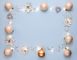 New year 2021. Merry Christmas and Happy Holidays greeting card. Christmas composition. Gold decorations on pastel blue background. Winter, new year concept. Flat lay, top view, copy space