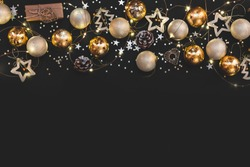 New year 2020. Merry Christmas and Happy Holidays greeting card. Christmas composition. Gold and silver decorations on black background. Winter, new year concept. Flat lay, top view