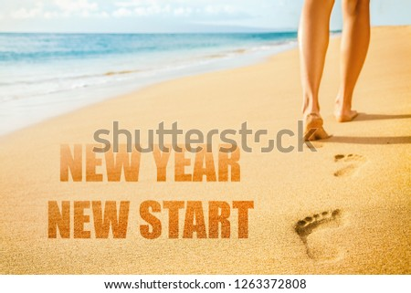 New Year 2019 New Start resolution concept. Beach woman legs feet walking barefoot on sand leaving footprints in sunset. Vacation travel freedom people.