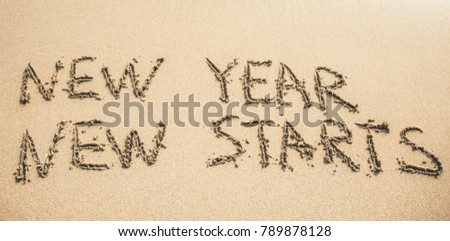 New Year New Starts text written on the sand #789878128