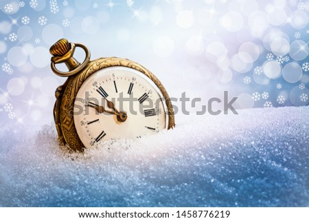 New year old gold clock before midnight. Antique pocket watch in the snow. Holiday concept