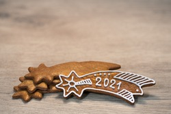 New Year 2021 on ornate gingerbread Bethlehem star for good luck laid on wood background. Gold baked Christmas cookie decorated by sugar icing. Stacked sweets in artistic still life. Selective focus.