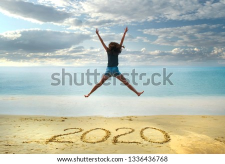 New Year 2020 on the sand,happy girl with hands up jumping on the beach #1336436768