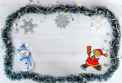 New Year or Christmas holidays decoration with green decorative ribbon, snowflake ornaments, snowman and a happy Santa Claus on a white wooden pattern. Seasonal festive greeting card. Copy space.