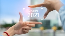 New year 2021 or start straight concept.Business woman making frame round and word vision 2021 with her hands.Concept of planning and challenge or career path,business strategy,opportunity and change