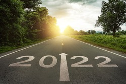 New year 2022 or straightforward concept. Text 2022 written on the road in the middle of asphalt road at sunset.Concept of planning and challenge, business strategy, opportunity ,hope, new life change