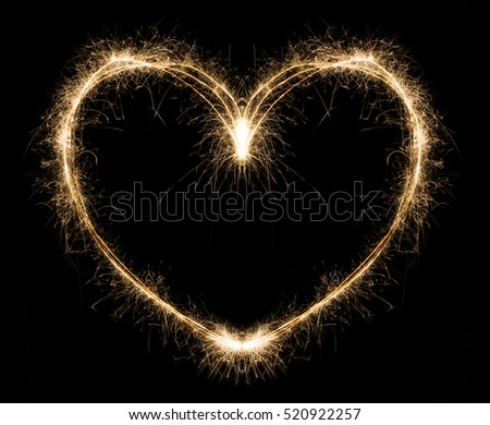New year party burning sparkler heart shape on black background. Glowing holiday sparkling hand fireworks, love symbol shining fire flame. Christmas light. #520922257