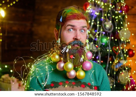 New year party. Surprised Santa man with decorated beard. Christmas decorations. Santa Claus man with decorated beard. Decorated beard. Christmas beard decorations. Merry Christmas and happy new year.