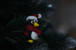 new year penguin in a santa claus  hat with pompon and red scarf sits on the christmas tree and looks to the left