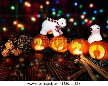 New Year picture. Toy white bear and penguin on the background of multi-colored lights of a garland with tangerine lights 2020.