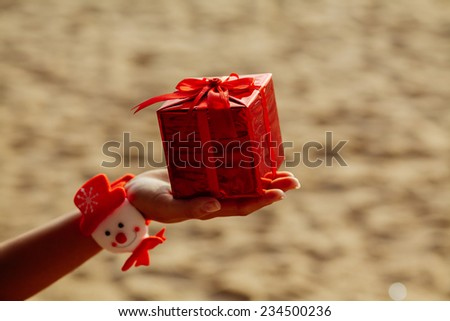 new year present gift in red box in hand on the beach in tropics / christmas gift in red box on the beach
