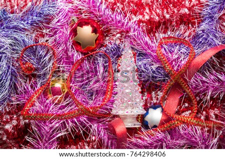 New Year 2018 red ribbon with Christmas balls and tree on a background of tinsel #764298406