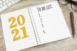 New Year resolution Goal list 2021 on wooden desk with notebook written in handwriting about plan listing of new year goals and resolutions setting.