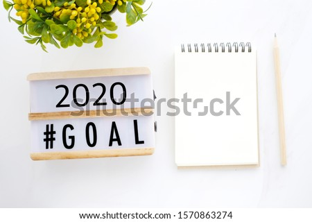 New year resolution, 2020 goals on wood box and blank notebook paper on white marble background, business new year aim to success, banner, backdrop, mock up, template, poster, wallpaper