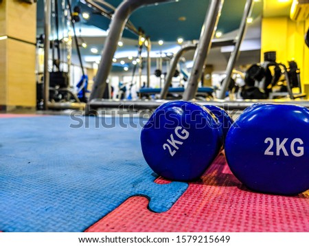 New Year resolution to start going to the gym and healthier lifestyle with closeup of small 2 kg dumbbells in blue color on rubber ground in a well equipped interior gym