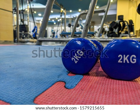 New Year resolution to start going to the gym with closeup of small 2 kg dumbbells in blue color on rubber ground in a well equipped interior gym