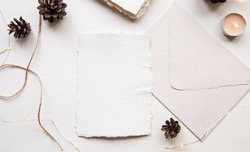 New Year resolution, wish list concept. Blank letter mock up on handcrafted paper. Letter envelope, pine cones, craft thread and candle. Pastel, beige colors, cozy hygge style. Flat lay, top view.