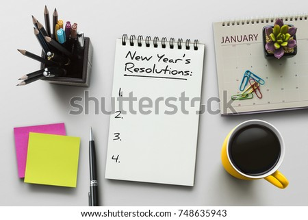New Year resolutions, goals or action plan concept. Notebook on office table with calendar, coffee, plant and stationery. Flat lay (top view) notepad for input copy or text on white background.