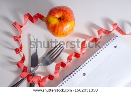New year resolutions notebook fork and knife an apple. Losing weight concept