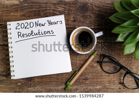 New year resolutions 2020 on desk. 2020 goals with notebook, coffee cup and eyeglasses on wooden background. Goal, plan, strategy, action, idea concept