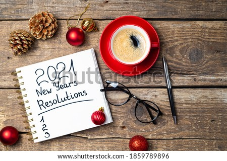 New year 2021 resolutions on desk. 2021 goals with notebook, coffee cup, eyeglasses, Christmas ornaments on wooden background. Goals, plan, strategy, action, idea concept. 2021 template, copy space