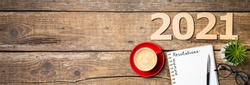 New year resolutions 2021 on desk. 2021 resolutions with notebook, coffee cup, succulent,  eyeglasses on wooden background. Goals, plan, strategy, list, idea concept. New Year 2021 template,copy space