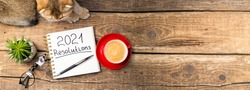 New year resolutions 2021 on desk. 2021 resolutions with notebook, cute cat, coffee cup, eyeglasses, succulent on wooden background. Goals, plan, strategy, list, idea, cozy home concept. Copy space