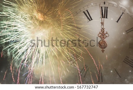 New Year\'s at midnight  - fireworks, and clock close to midnight