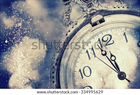 New Year\'s at midnight - Old clock with fireworks and holiday lights