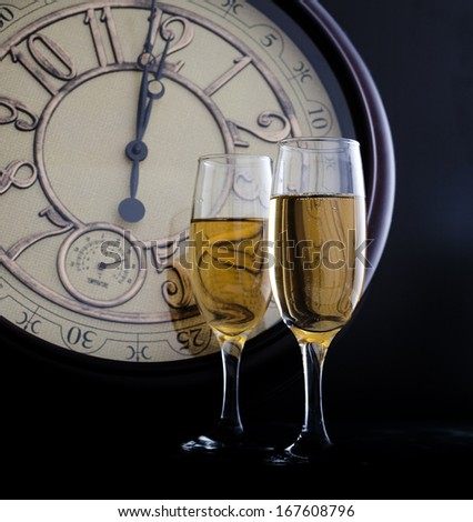 New Year\'s at midnight with champagne glasses and clock on light background