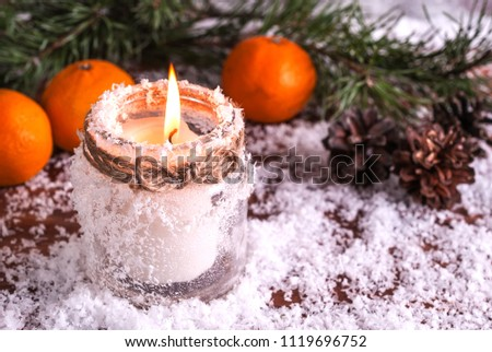 Stock Photo New Year's card with a candle, fir branches and yellow tangerines on a snow-covered background