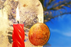 New Year's decoration. Bitcoin sunk into the ice and brightened by the flame of a red candle against the background of Christmas tree branches and a blue sky. The freezing of financial assets.
